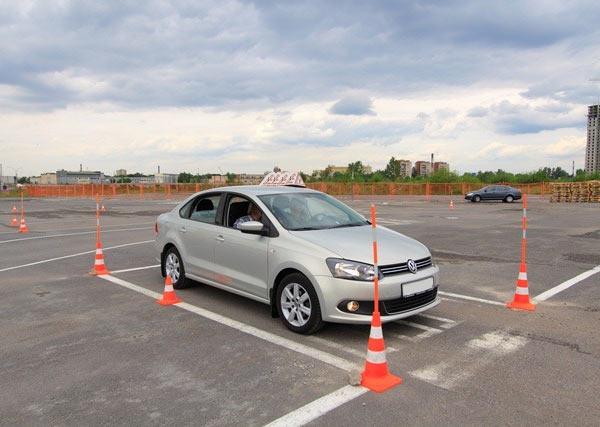 Специальная площадка для обучения вождению. Начинающий водитель практикуется навыка параллельной парковке задним ходом